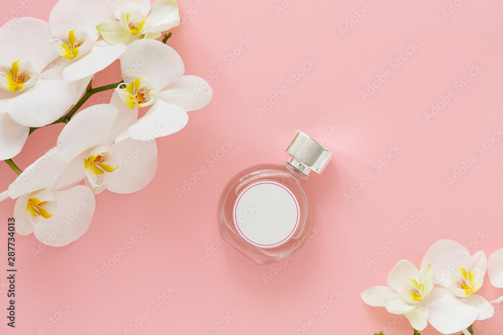 Fototapety, obrazy: Perfume bottle with white orchid.  Top view of bottle of perfume surrounded with flowers on pink background. Perfumery, fragrance collection. Free space for text.