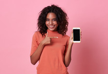 Portrait Of A Happy Young African Woman Hand Pointing At  Blank Screen Mobile Phone Isolated Over Pink Background.