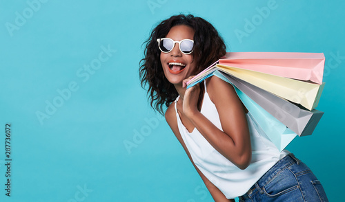 Vászonkép Portrait of an excited young african woman hand holding shopping bag isolated over blue background