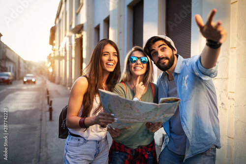 Obraz na płótnie Happy friends enjoying sightseeing tour in the city