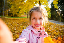 Cute Little Girl With Missing Teeth Taking Selfie. Happy Child Laughing And Smiling. Sunny Autumn Forest, Sun Beam.