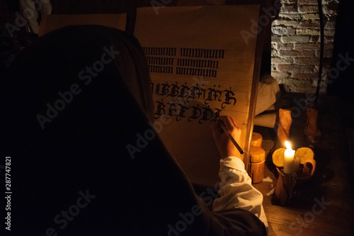 The hands of a medieval monk who write a manuscript by candlelight Fototapet