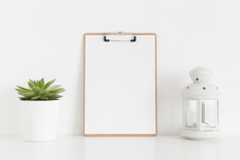 Wooden Clipboard Mockup With A Succulent Plant And A Candle Holder On A White Table.