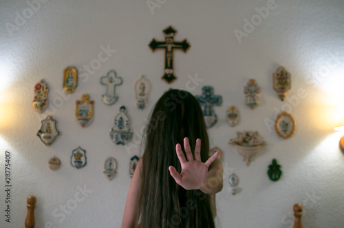 Young girl with long mane in front of her face sitting on the bed shows the palm Fototapeta