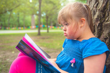 A Portrait Of Trisomie 21 Child Girl Outside Having Fun On A Park Reading Book