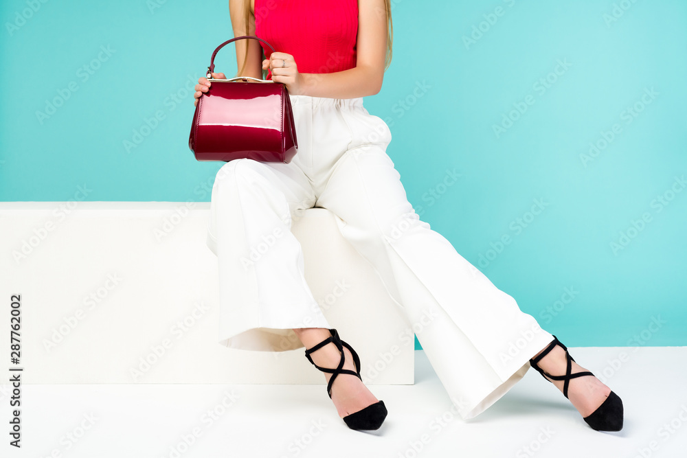 Fototapety, obrazy: Beautiful legs woman sitting on the bench. With red purse and high heel shoes.
