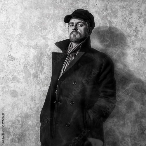 Valokuva  man with grungy blond hair  in  stylish black trench coat