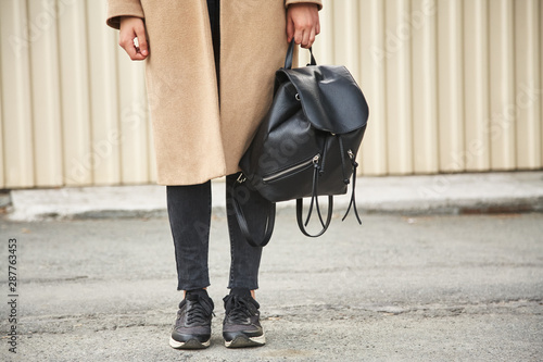 Fotografie, Obraz  A girl in a brown cashmere coat with a black backpack