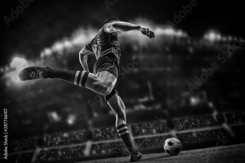 Cuadros en Lienzo  Football player with ball on field of stadium