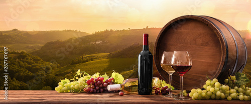 Aluminium Prints Alcohol Wineglasses With Grapes And Barrel On A Sunny Background