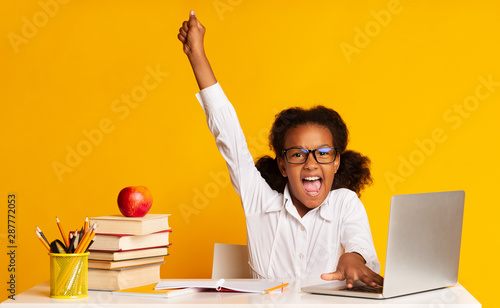 Fotografia, Obraz Afro Schoolgirl Raising Hand Sitting At Laptop In Studio