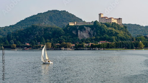 Wonderful view of the Rocca di Angera with a white sailboat sailing on Lake Magg Billede på lærred