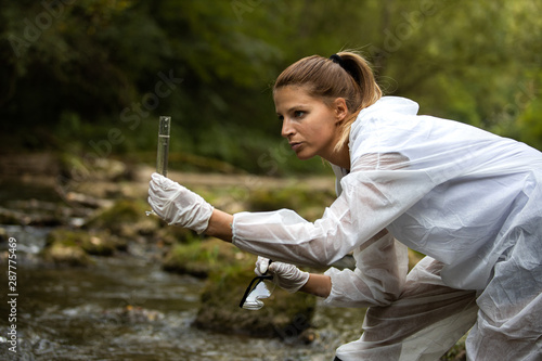 Scientist in protective suits takeing water samples from the river,stock photo Canvas-taulu