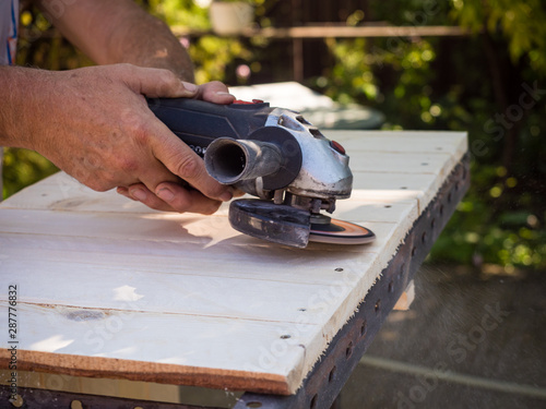 Man working with angle grinder and flap disc as a Sander on wooden shelf Fototapete