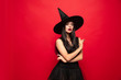 canvas print picture Young brunette woman in black hat and costume on red background. Attractive caucasian female model. Halloween, black friday, cyber monday, sales, autumn concept. Copyspace. Pointing up.