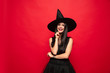 canvas print picture Young brunette woman in black hat and costume on red background. Attractive caucasian female model. Halloween, black friday, cyber monday, sales, autumn concept. Happy smiling.