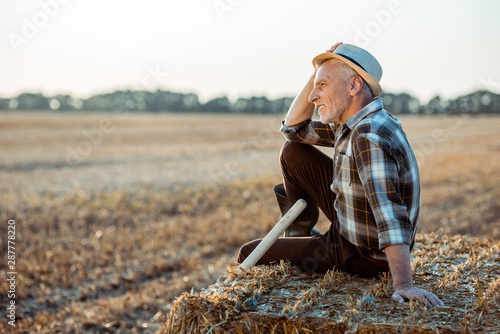cheerful bearded farmer sitting on bale of hay and touching straw hat Tablou Canvas