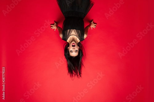 Poster Akt Young brunette woman in black hat and costume on red background. Attractive caucasian female model. Halloween, black friday, cyber monday, sales, autumn concept. Scary screaming upside down.