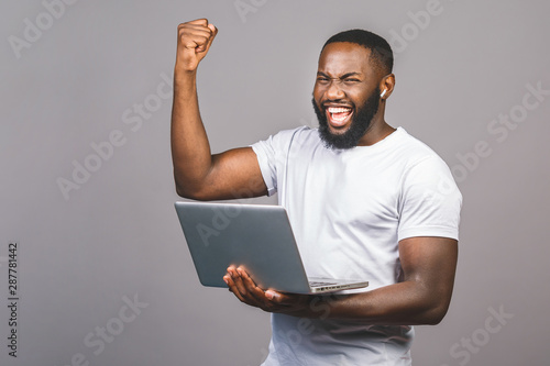 Excited happy afro american man looking at laptop computer screen and celebrating the win isolated over grey background Canvas Print