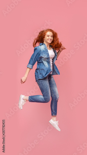 Fotografia Attractive redhead teen girl having fun, jumping on pink background