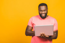 Young Smiling African American Man Standing And Using Laptop Computer Isolated Over Yellow Background.