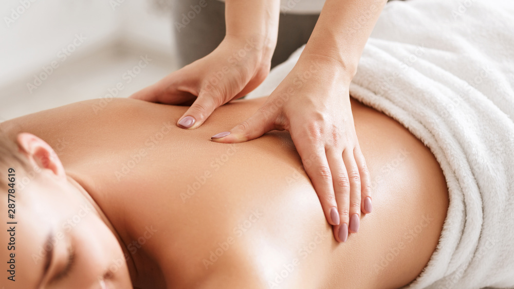 Fototapeta Body care. Young girl having massage, relaxing in spa salon