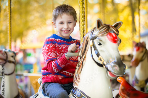 Obraz na plátně  Joyful child on a horse carousel