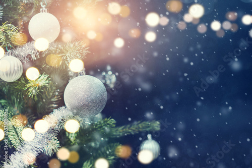Christmas holiday background. Silver bauble hanging from a decorated on tree with bokeh and snow, copy space.
