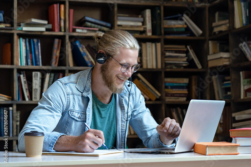 Fotografía Smiling happy young man wear wireless headset look at laptop screen make notes s