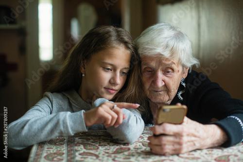 Fotografia, Obraz A little cute girl teaches her grandmother to use a smartphone..
