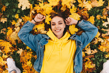 Autumn Walk. Woman Portrait. Happy Girl In Yellow Hoodie And Jean Jacket Is Looking At Camera And Smiling While Lying On The Ground In The Park; Top View