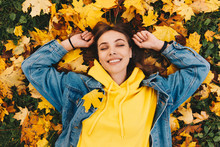 Autumn Walk. Woman Portrait. Happy Girl In Yellow Hoodie And Jean Jacket Is Smiling While Lying With Her Eyes Closed On The Ground In The Park; Top View