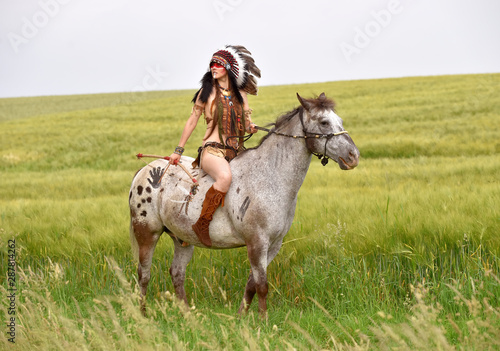 Photo A young Indian girl rides horseback through the prairie