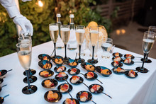 Appetizing Table With Cold Snacks On Stand And Tableware On Luxury Stand-up On A Festive Wedding Table Outdoor. Catering Service Plate.