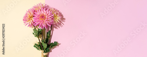 Foto Festive flower bouquet over pastel pink and yellow background, copy space