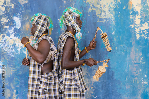 Fotografia African artists with traditional musical instruments on blue wall background