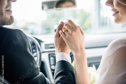 Fototapety, obrazy: cropped view of bridegroom and bride holding hands in car