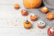 Festive Halloween Cupcakes Decorated Colored Decorations Witch Hat, Orange Cream, The Face Of A Ghost. Wooden Background With Pumpkin And Copy Space, Selective Focus.