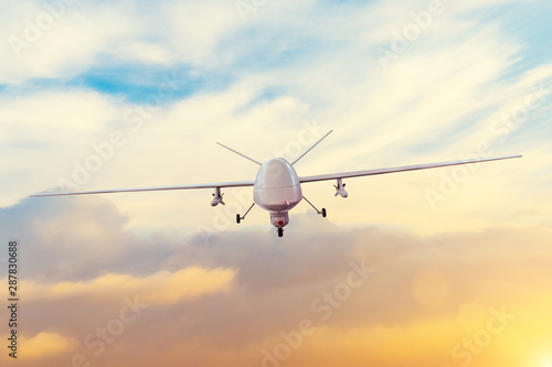 Obraz Unmanned military drone patrols the territory at sunset. The view is straight ahead. - fototapety do salonu