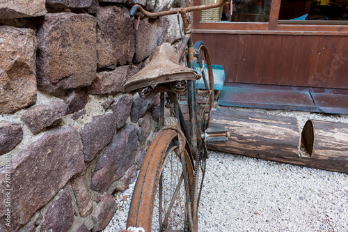 Fototapeta old rusty bicycle in front of a rock wall