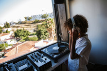 Young DJ With Headphones At The Turntable