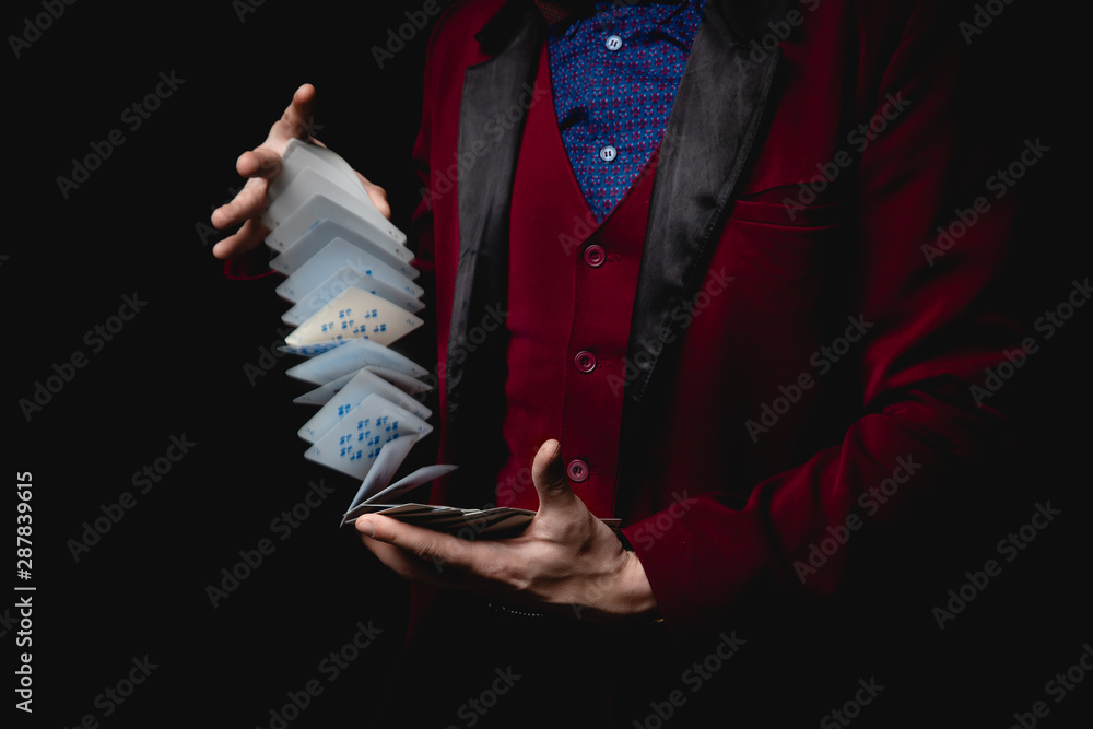 Fototapeta Magician shows trick with playing cards, dark background