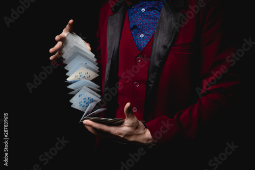 Obraz Magician shows trick with playing cards, dark background - fototapety do salonu