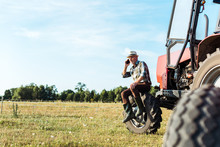 Selective Focus Of Agronomist Talking On Smartphone Near Tractor