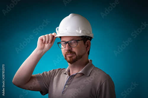 Photo  Male with goofy look, beard and glasses holding a protective construction helmet