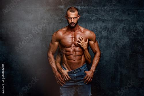 Pinturas sobre lienzo  Handsome Muscular Men Posing With Women Hands Around his Torso
