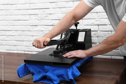 Ingelijste posters Eigen foto Man using heat press machine at table near white brick wall, closeup