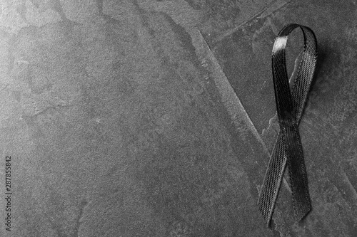 Fotografie, Obraz  Black ribbon on dark grey stone surface, top view with space for text