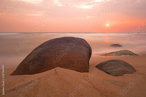 Slika na platnu Long exposure sunrise by a beach in Tayrona National Park with boulder rocks, Cartagena, Colombia