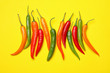 Leinwanddruck Bild - Different hot chili peppers on yellow background, flat lay